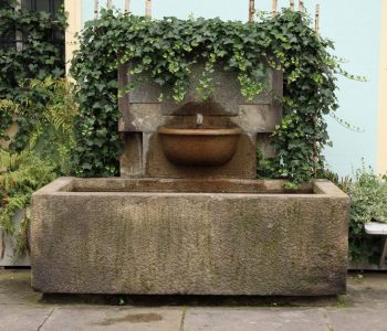 Old wall fountain with a stone bowl covered with ivy